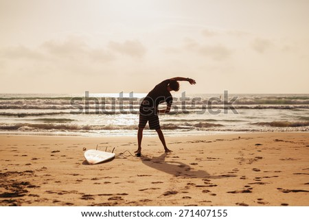 surfer man fitness stretching on beach silhouette back view - stock photo