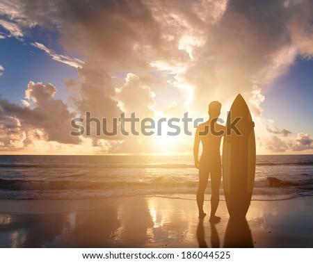 surfer man standing on  beach watching the sunrise - stock photo