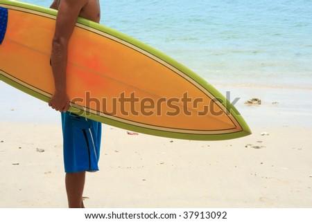 Surfer on beach with vintage retro orange surfboard - stock photo