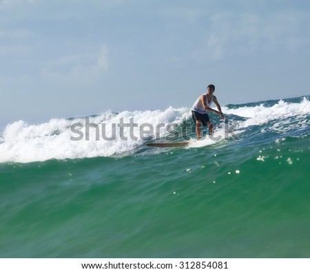 Surfer on longboard rides a beautiful blue wave in the sea.