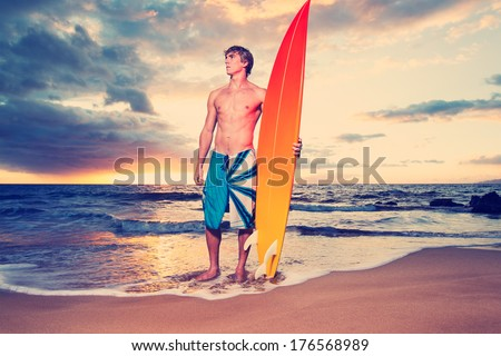 Surfer on the beach at sunset in Hawaii
