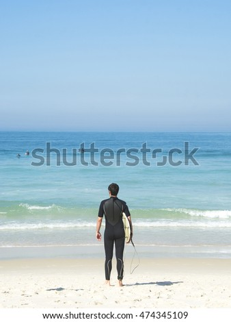 Surfer on the beach holding his surfboard and watching the sea