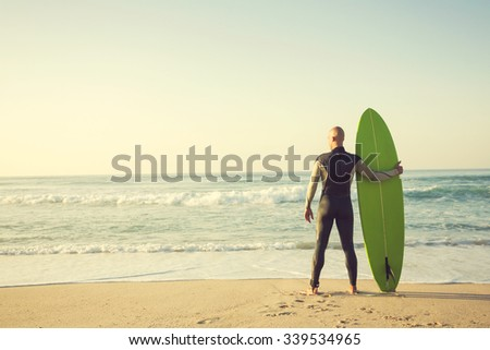 Surfer on the beach holding is surfboaerd and watching the waves