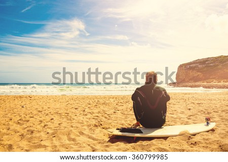 surfer on the beach waiting for perfect waves - stock photo