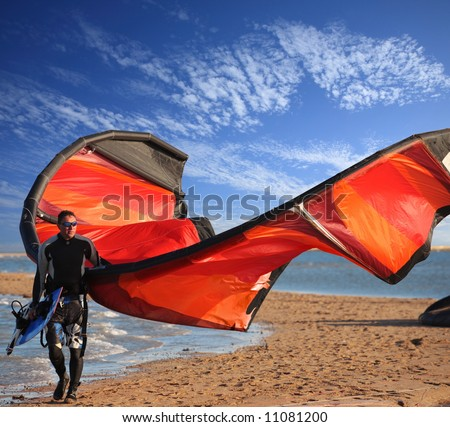 surfer on the beach with his board and  red  kite on deep blue sky background - stock photo