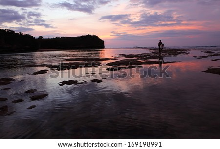 surfer on the low water of ocean  at sunset on Bali island, Indonesia - stock photo