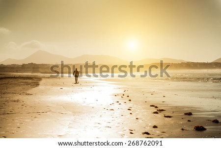 Surfer on the ocean beach at sunset on  Canary Islands. Lanzarote, Spain. - stock photo