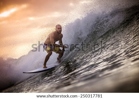 Surfer on Wave at Sunset - stock photo