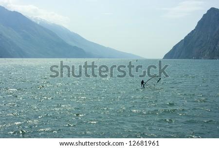 Surfer practicing sports activity on Garda lake - stock photo
