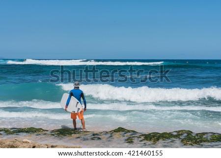 Surfer ready to surf on Maui, Hawaii - stock photo
