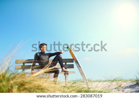 Surfer relaxing on a wooden bench on a sand-dune with coastal grasses with his surfboard balanced against the seat, skyline view with hot summer sun