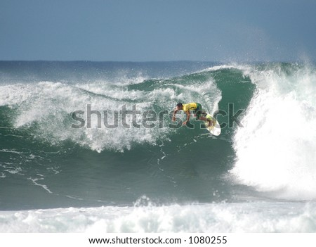 Surfer rides a wave at Bonzai Pipeline off of Oahu's North Shore. - stock photo