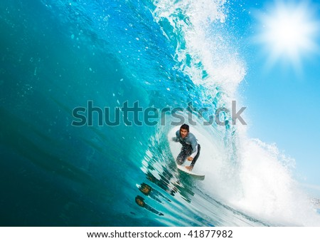 Surfer rides Big Wave, In the Tube with Sunny Blue Sky - stock photo