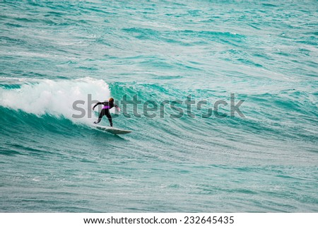 surfer riding a wave in the blue sea. Shot in Sardinia, Italy