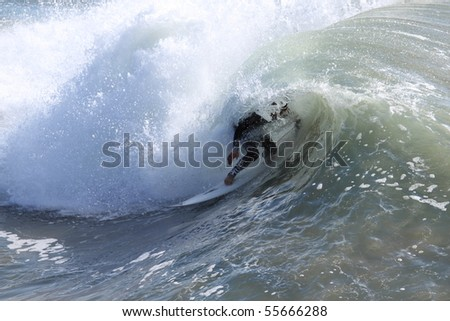 Surfer riding a wave in the Pacific Ocean - stock photo