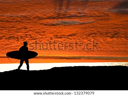 Surfer running on the cliffs at Santa Cruz, heading for the Pacific ocean as the sun sets to get in one final ride - stock photo