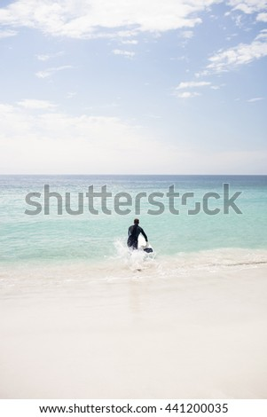 Surfer running towards sea with a surfboard on a sunny day - stock photo