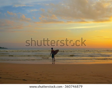 Surfer silhouette at ocean sunset beach - stock photo