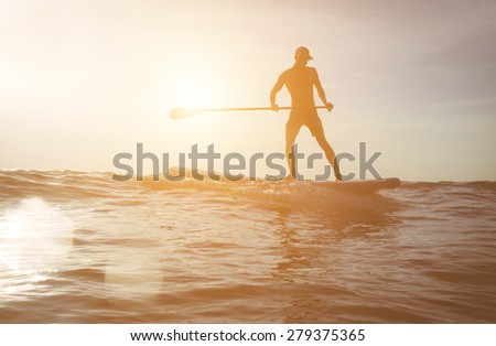 surfer silhouette at sunset.image with lens flare included for an artistic touch. concept about sport, surf, vacations and people - stock photo