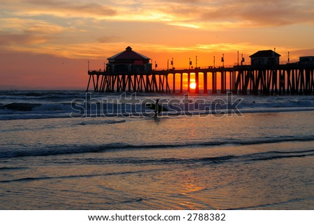 Surfer Silhouette In Foreground of Pier At Sunset - stock photo