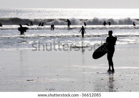 surfer silhouette on a beach - stock photo