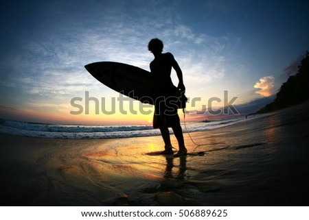 Surfer silhouette with surf board standing on beach at sunset with ocean waves rolling in