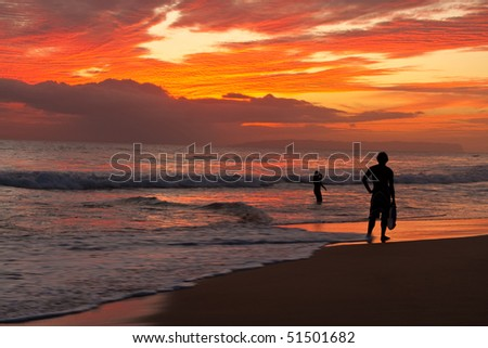Surfer silhouetted on tropical ocean beach at sunset - stock photo