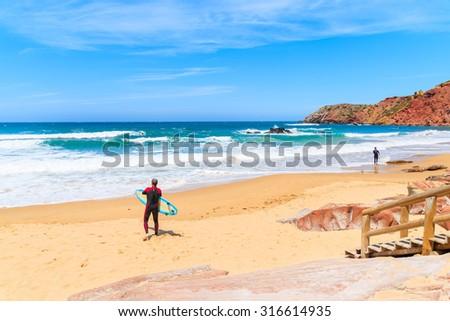 Surfer standing on Praia do Amado beach with ocean waves hitting shore, Algarve region, Portugal - stock photo