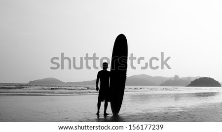 Surfer standing on the beach, close to the sea, contemplating the waves - stock photo