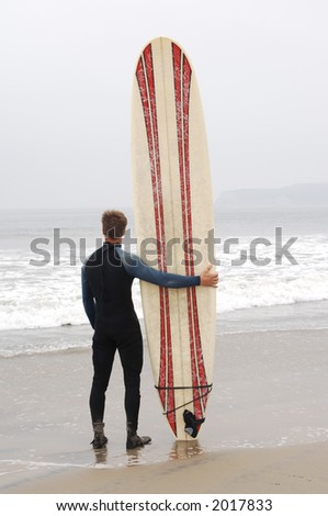 surfer standing on the beach with surfboard looking out to sea - stock photo