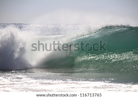 Surfer tube riding a wave in Supertubos, Peniche, Portugal - stock photo