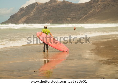 surfer wait for a wave at the coastline - stock photo