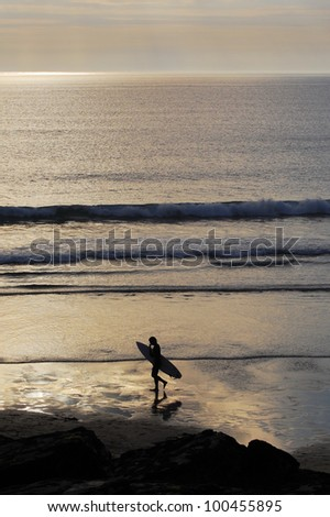 Surfer walking accross the beach at sunset. Trebarwith Strand, Cornwall, UK. - stock photo