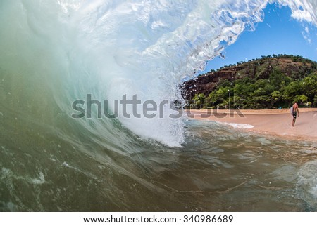 Surfer walking away from wave in Maui, Hawaii - stock photo