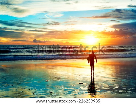Surfer walking on the beach in sunset light. Bali island, Indonesia  - stock photo