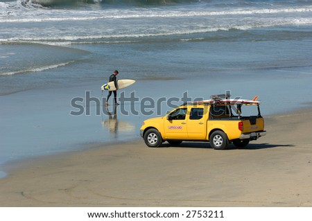Surfer Walks Beach in Southern California - stock photo