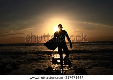 Surfer Walks Down Beach at Sunset - stock photo