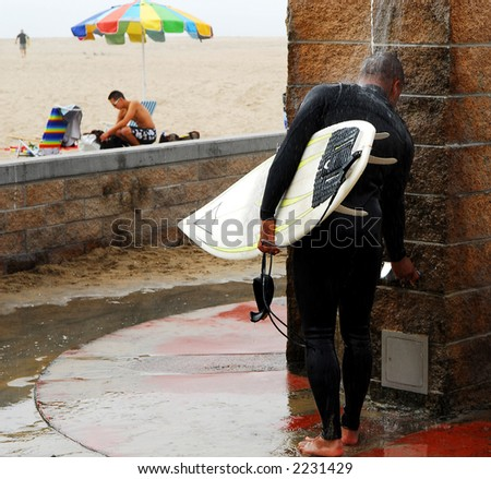 Surfer washes away sand under shower next to beach.