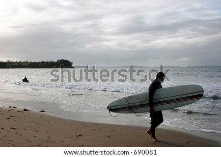 Surfer watching the waves at Milford Beach - stock photo