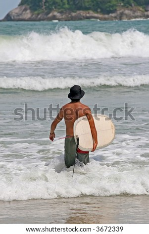 Surfer wearing a hat makes his way into the waves in Phuket, Thailand