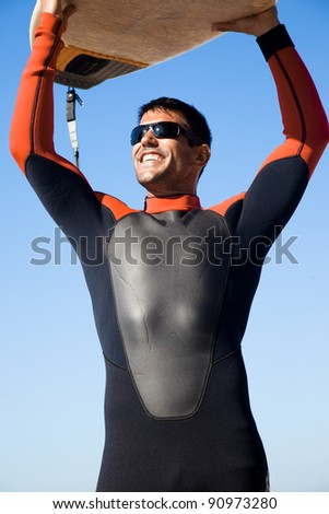 Surfer wearing a wet suit holding his surf board above his head. - stock photo