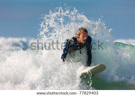 Surfer with his board in the wild waves - stock photo