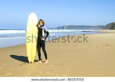 Surfer with his surfboard at the beach - stock photo