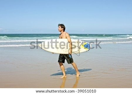 Surfer with his surfboard at the beach ready to surf - stock photo