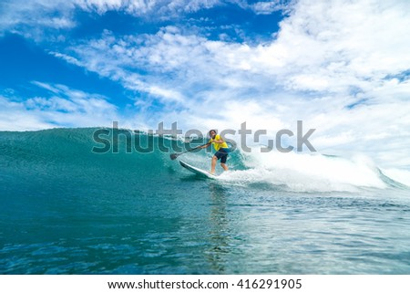 Surfer with long white hair rides by paddle board (S.U.P) in the big ocean wave in Mauritius Island, Indian Ocean