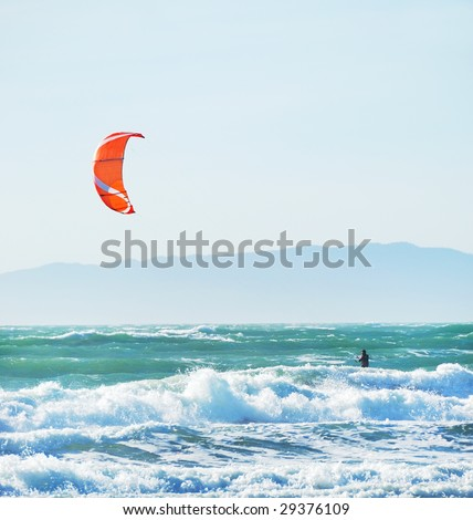 Surfer with red kite surfing off the beach in San Francisco, California on a sunny day.