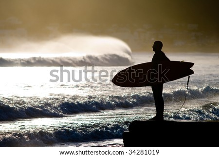 surfer with surfboard looking at waves