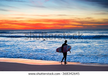 Surfer with surfboard walking on the beach at majestic sunset - stock photo