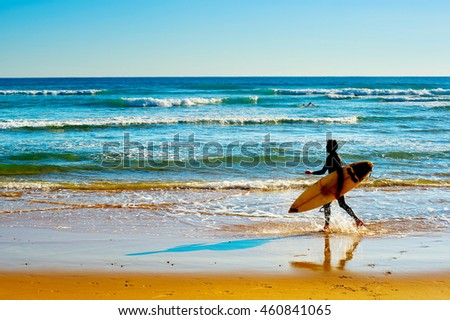 Surfer with surfboard walking on the ocean beach