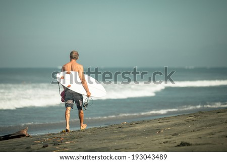 surfer with surfboard walks along the beach in the day time - stock photo